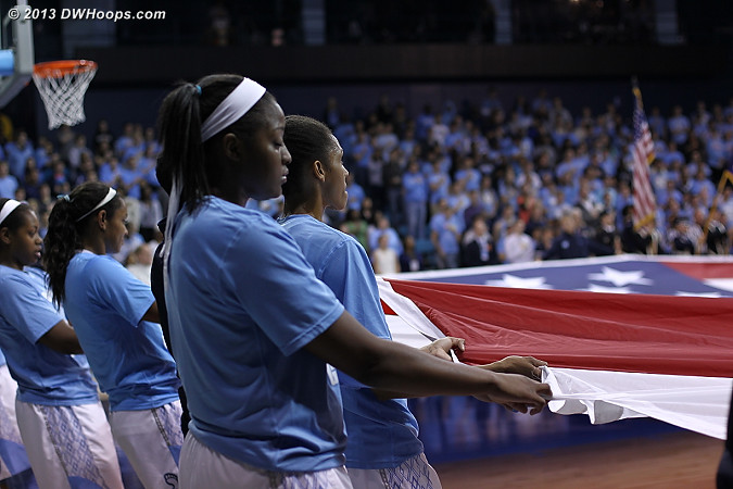 UNC team members stretch a huge American flag across the court for the national anthem on Veterans Day